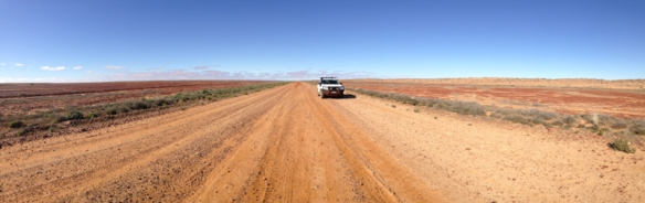 Our offroad vehicle parked on the Birdsville Track, surrounded by the Simpson Desert